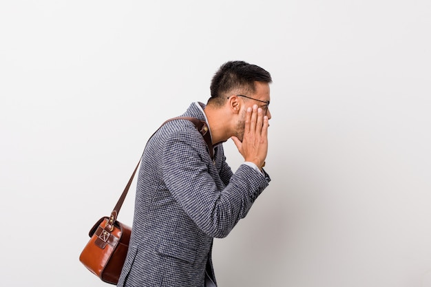 El joven hombre de negocios filipino contra una pared blanca grita fuerte, mantiene los ojos abiertos y las manos tensas.