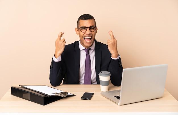 Joven hombre de negocios en su oficina con una computadora portátil y otros documentos con los dedos cruzados