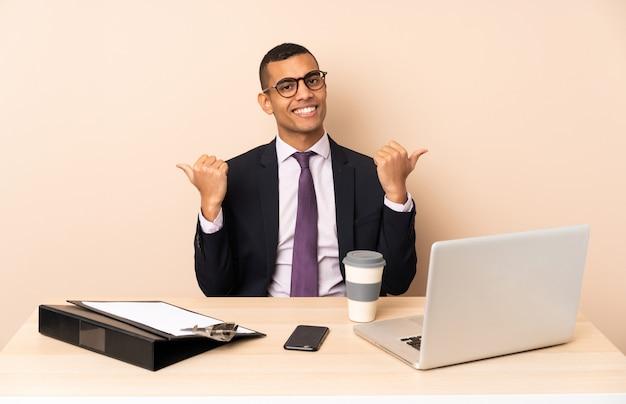 Joven hombre de negocios en su oficina con una computadora portátil y otros documentos con pulgares arriba gesto y sonriendo