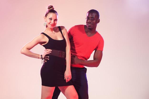 El joven hombre negro y mujer blanca está bailando