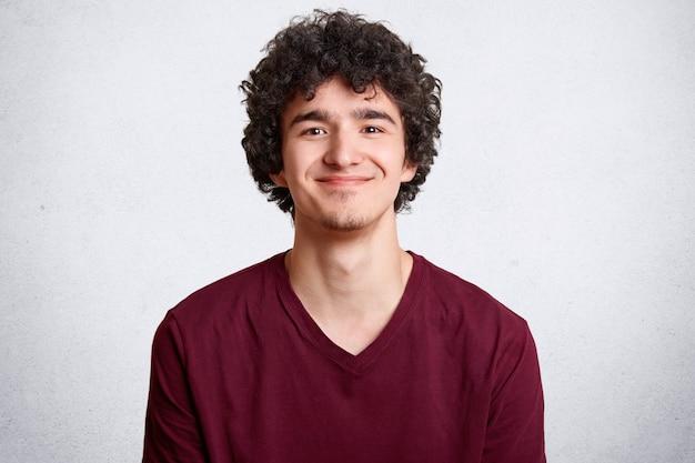 Joven hombre positivo con cabello rizado