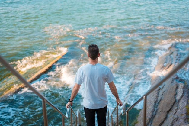 Joven hombre de raza blanca en las escaleras que conducen al mar