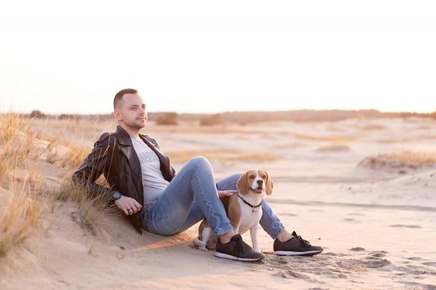 Joven hombre de raza caucásica vestido con chaqueta de cuero negro y jeans azul se sienta en la playa de arena junto a su amigo el perro de raza beagle.