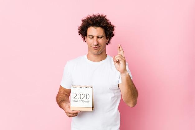 Joven hombre rizado caucásico sosteniendo un calendario 2020 cruzando los dedos para tener suerte