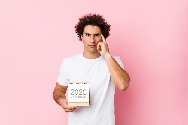 Joven hombre rizado caucásico sosteniendo un calendario 2020 señalando su sien con el dedo, pensando, centrado en una tarea.