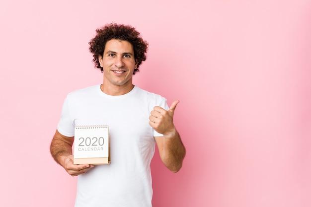 Joven hombre rizado caucásico sosteniendo un calendario 2020 sonriendo y levantando el pulgar hacia arriba