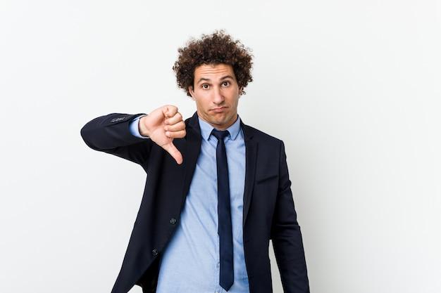 Joven hombre rizado de negocios contra el fondo blanco que muestra un gesto de disgusto, pulgares abajo