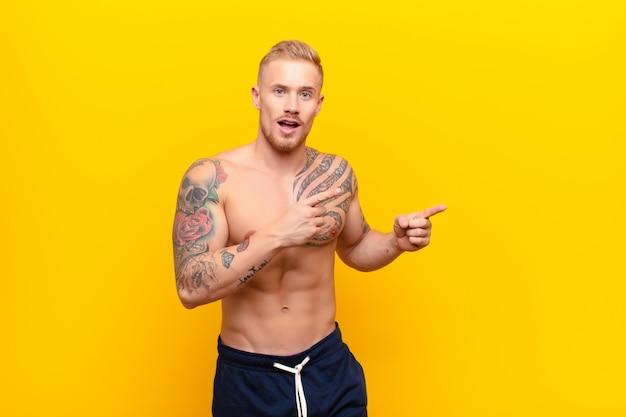Joven hombre rubio fuerte sintiéndose alegre y sorprendido, sonriendo con una expresión de asombro y apuntando hacia un lado contra la pared amarilla