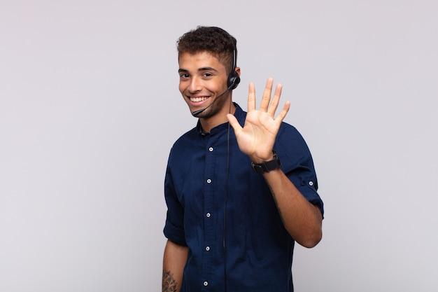Joven hombre de telemercadeo sonriendo y mirando amistosamente, mostrando el número cinco o quinto con la mano hacia adelante, contando hacia atrás