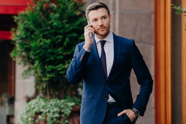 Joven hombre tiene conversación telefónica, mira con confianza a distancia