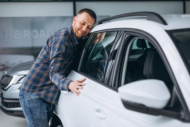 Joven huggingf un automóvil en una sala de exposición de automóviles
