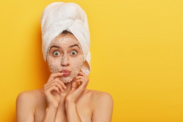 Joven impresionada mantiene los labios redondeados, los ojos bien abiertos, se aplica un exfoliante de sal marina, usa una toalla envuelta en la cabeza, tiene una piel delicada y suave, modelos de interior. gente, spa, peeling, concepto de frescura.