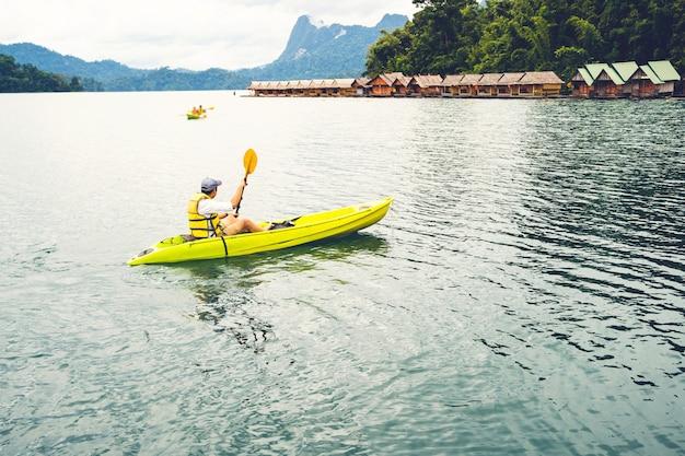 Joven inconformista disfruta de kayak en el lago mientras que las vacaciones de verano