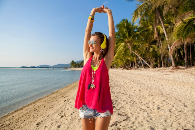 Joven inconformista hermosa mujer, playa tropical, vacaciones, colorido, estilo de tendencia de verano, gafas de sol, auriculares, escuchar música, fondo de palmeras, sonriendo feliz, diversión, detalles, retrato de cerca