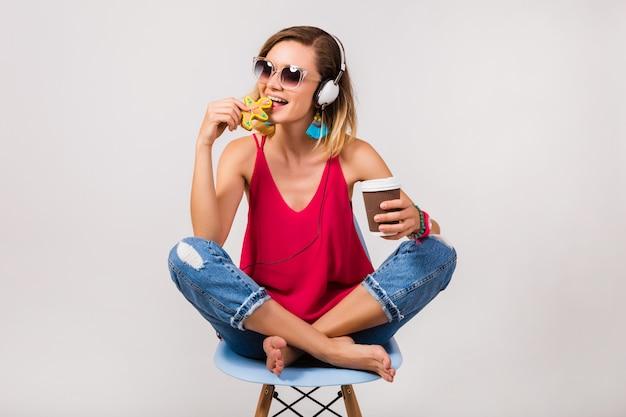 Joven inconformista hermosa mujer sentada en una silla y comiendo galletas