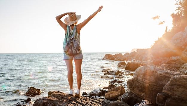 Joven inconformista mujer sombrero rukzak con las manos en alto, de pie en el acantilado mirando el mar al atardecer.