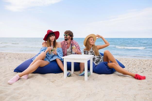 Joven inconformista sonriente compañía de amigos de vacaciones sentados a la mesa en la cafetería de la playa bebiendo cócteles mojito