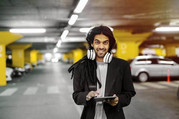 Joven inconformista urbano lindo hombre con tableta. de pie en el garaje con auriculares alrededor del cuello.