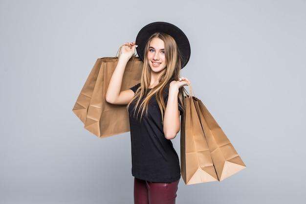 Joven inconformista vestida con camiseta negra y pantalones de cuero sosteniendo bolsas de compras artesanales en blanco con asas aisladas en blanco
