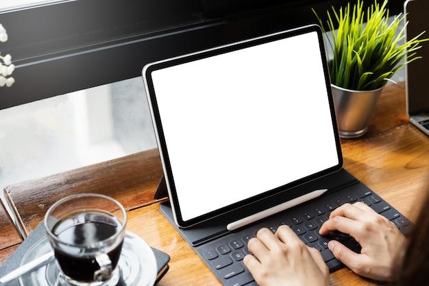 Joven independiente con una tableta de pantalla en blanco maqueta en el espacio de trabajo conjunto.