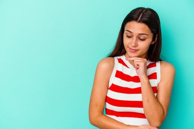 Joven india aislada en la pared azul mirando hacia los lados con expresión dudosa y escéptica.