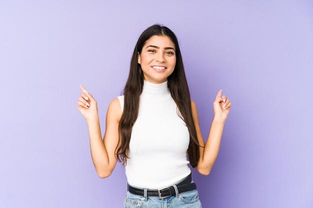 Joven india aislada en la pared violeta apuntando a diferentes espacios de copia, eligiendo uno de ellos, mostrando con el dedo.