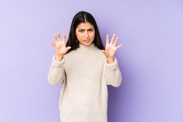 Joven india aislada en la pared violeta mostrando garras imitando a un gato, gesto agresivo.