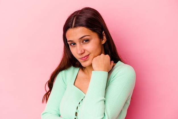 Joven india aislada sobre fondo rosa confundida, se siente dudosa e insegura.