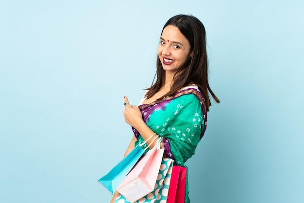 Joven india con bolsas de compras apuntando hacia atrás
