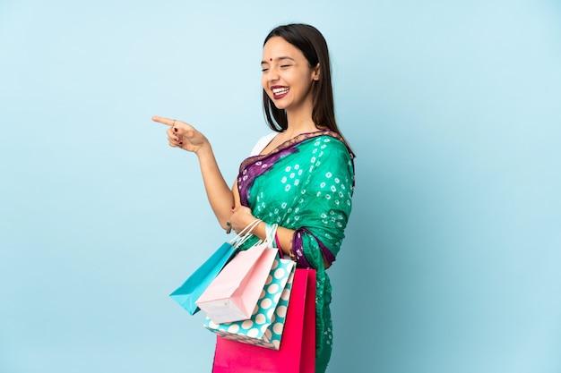Joven india con bolsas de compras apuntando con el dedo hacia un lado y presentando un producto