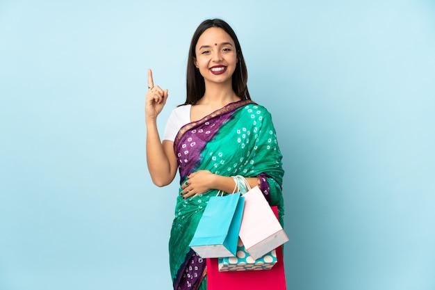 Joven india con bolsas de compras apuntando hacia una gran idea