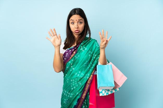 Joven india con bolsas de compras contando nueve con los dedos