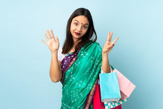 Joven india con bolsas de compras contando ocho con los dedos
