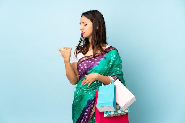 Joven india con bolsas de compras infelices y apuntando hacia un lado