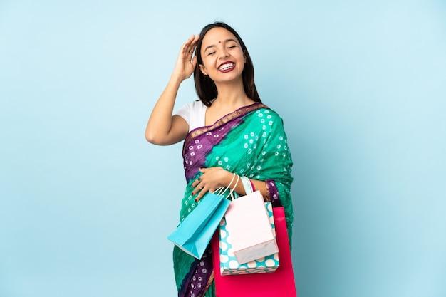 Joven india con bolsas de compras sonriendo mucho