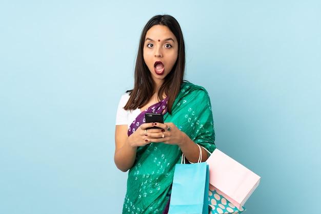 Joven india con bolsas de compras sorprendida y enviando un mensaje