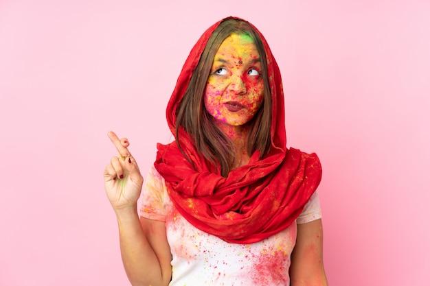 Joven india con coloridos polvos de holi en la cara en la pared rosa con los dedos cruzados y deseando lo mejor