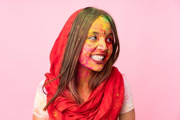 Joven india con coloridos polvos de holi en la cara en la pared rosa