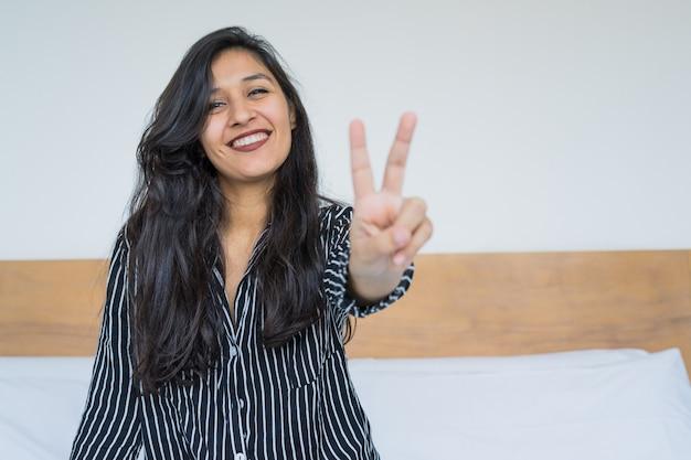 Joven india haciendo gesto de victoria en el dormitorio