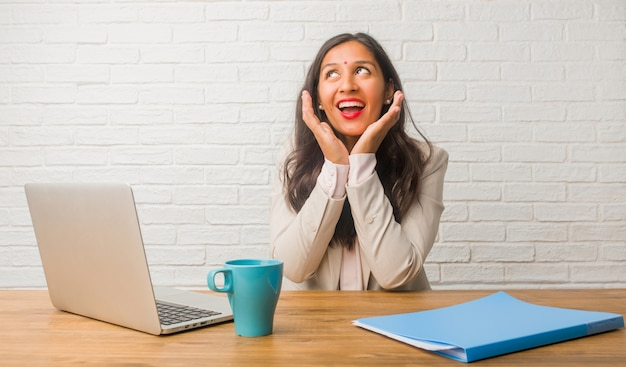 Joven india en la oficina sorprendida y conmocionada, mirando con los ojos bien abiertos, emocionada por una oferta o por un nuevo trabajo, gana el concepto