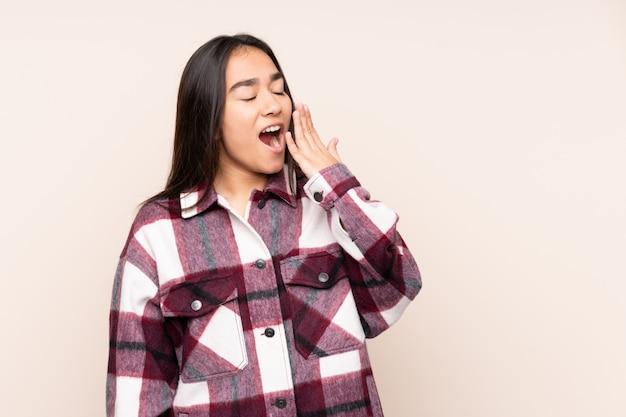 Joven india en pared beige bostezando y cubriendo la boca abierta con la mano