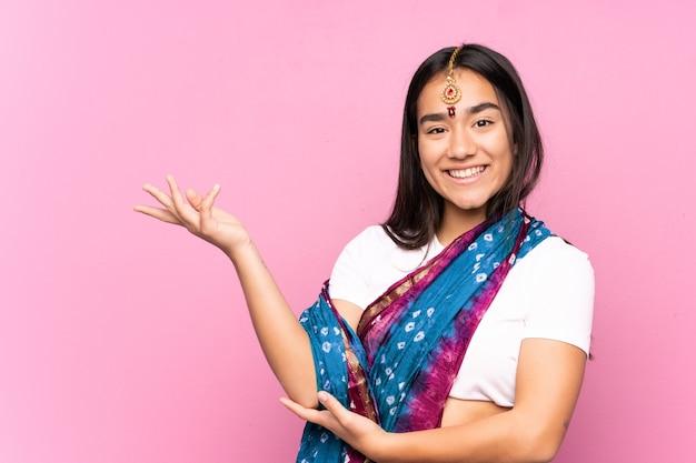 Joven india con sari sobre aislados extendiendo las manos hacia el lado para invitar a venir