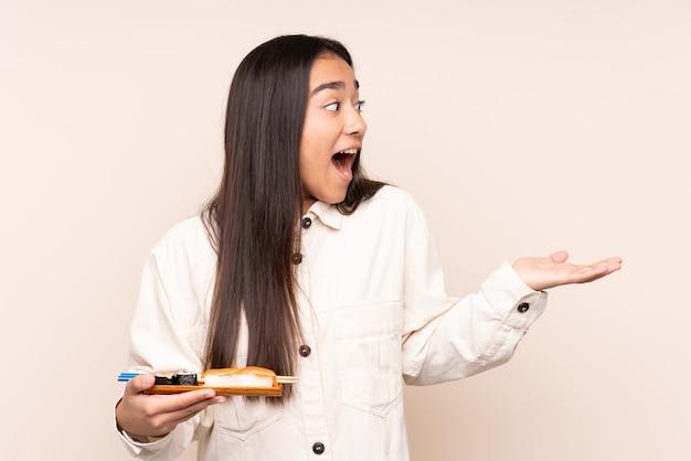 Joven india sosteniendo sushi aislado sobre fondo beige con expresión facial sorpresa