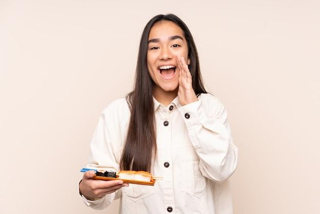 Joven india sosteniendo sushi aislado sobre fondo beige gritando con la boca abierta