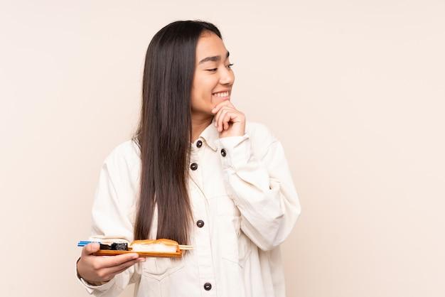 Joven india sosteniendo sushi aislado sobre fondo beige pensando en una idea y mirando de lado