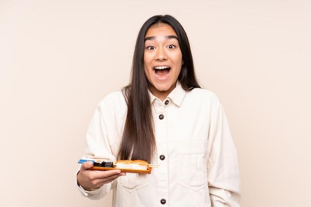 Joven india sosteniendo sushi aislado sobre fondo beige con sorpresa y expresión facial conmocionada