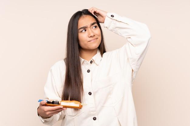 Joven india sosteniendo sushi en pared beige con dudas y con expresión de la cara confundida