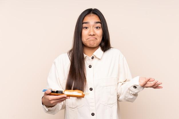 Joven india sosteniendo sushi en pared beige haciendo dudas gesto mientras levanta los hombros