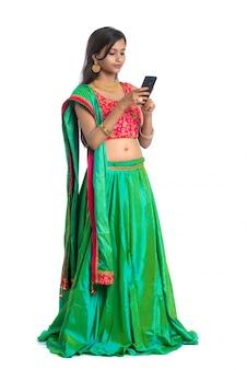 Joven india tradicional utilizando un teléfono móvil o teléfono inteligente aislado en un blanco