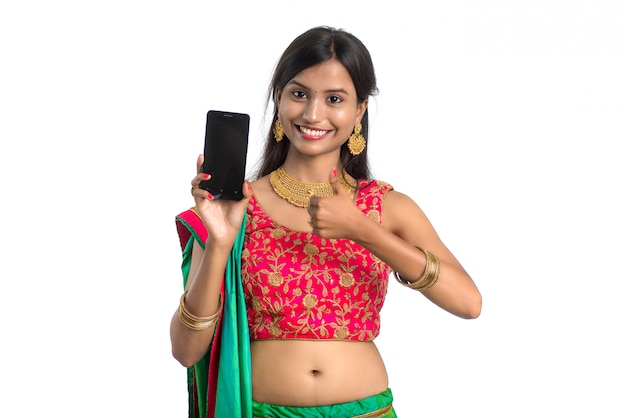 Joven india tradicional utilizando un teléfono móvil o teléfono inteligente y mostrando la pantalla en blanco del teléfono inteligente sobre fondo blanco.